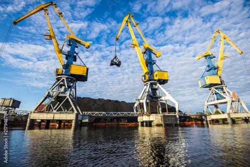 Leinwanddruck Bild A view of the port cranes against blue sky. Riga, Latvia