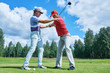 Golf training. Instructor trains new player in summer