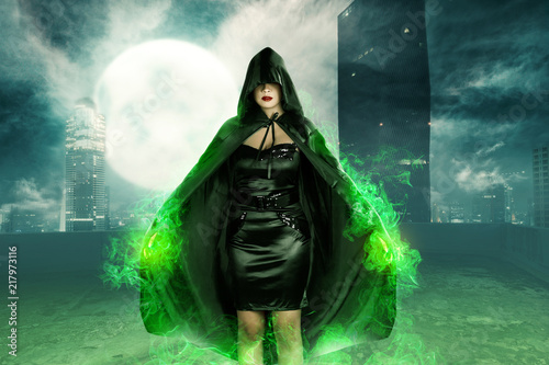 Fototapeta Young asian witch woman standing with green fire on her