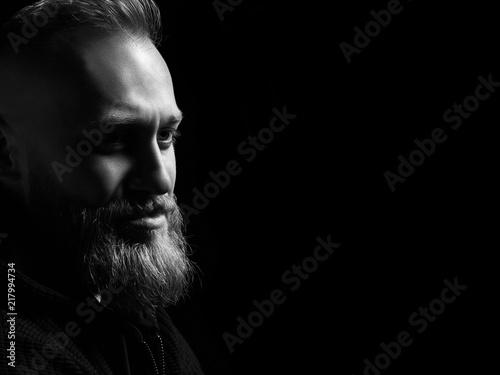 Czarny i biały męski portret z brodą na czarnym tle