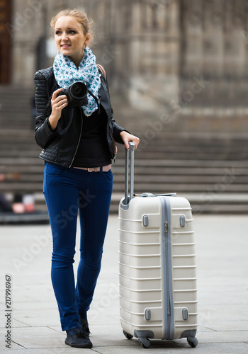 Poster woman walking in autumn city with digital camera