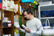 Smiling positive male customer buying flea treatment and shampoo
