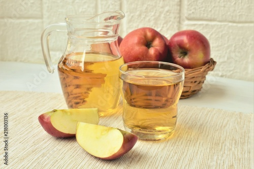 Aluminium Sap Apple juice in a glass and pitcher, fresh apples in a basket, on a veranda table.