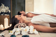 Leinwanddruck Bild - Young man and woman lying down on massage beds at Asian luxury spa and wellness center