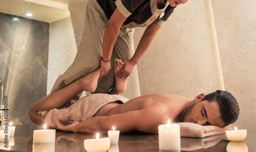 Leinwanddruck Bild Thai massage practitioner massaging young man through traditional stretching techniques in a luxury spa and wellness center