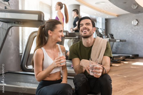 Leinwanddruck Bild Cheerful young man and woman with a healthy lifestyle drinking plain water for hydration during break at the fitness club