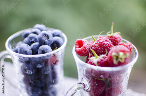 Foto Murales A glass of sweet red raspberries and blueberries