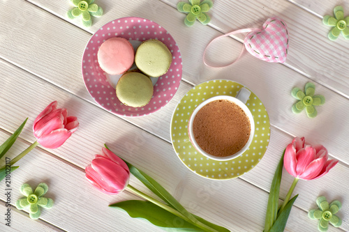 Plexiglas Macarons Spring coffee background. Macarons, espresso in pink cup, freesias and pink tulips