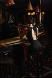 elegant lady in black dress, in restaurant at a bar - 218025106