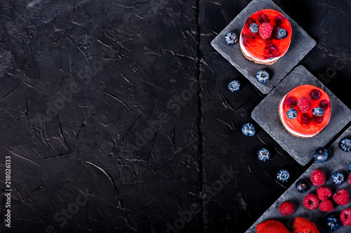 Foto Murales Cake with jelly, blueberries, raspberries and strawberries on a black background