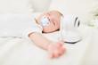 Leinwanddruck Bild - Baby schläft mit Babyphon am Babybett