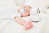 Baby schläft mit Babyphon am Babybett - 218026558