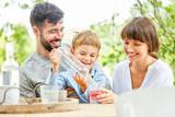 Junge sitzt mit seinen Eltern am Gartentisch - 218026576