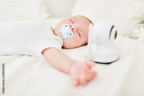Leinwanddruck Bild Baby schläft mit Babyphon am Babybett