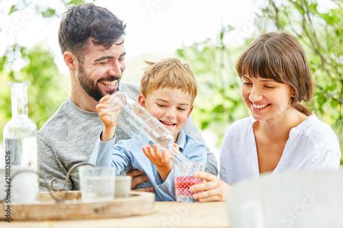 Junge sitzt mit seinen Eltern am Gartentisch