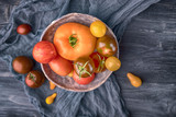 Ceramic bowl with various colorful tomatoes on wooden background. Top view, free space - 218027748