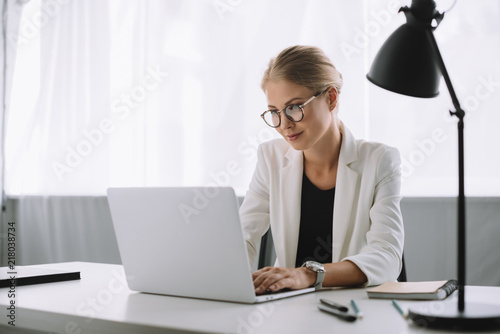 Fridge magnet portrait of businesswoman working on laptop at workplace in office