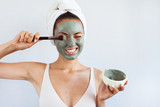 Young beautiful woman in face mask of therapeutic blue mud. Spa treatment, self care and healthy skin - 218041520