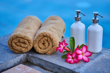 Plumeria flowers, spa cosmetic and towels over blue water background, spa still life, travel and tourism, conceptual photo of a summer vacation. © eskstock