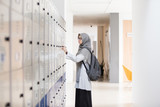 Asian hijab student standing next to locker and try to open her locker at college - 218046711