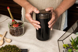 Women's hands grinding coffee beans in black coffee-grinder. Close up. - 218048744
