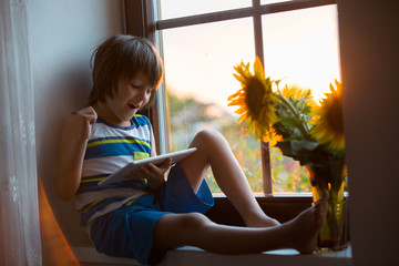 Cute little toddler child, playing on tablet on a window