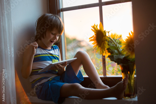 Foto Murales Cute little toddler child, playing on tablet on a window