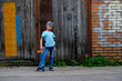 Beautiful young boy standing with a skateboard, against the background of the urban wall. Children ride on the Board in the street. Active lifestyle, sports, training, fresh air.