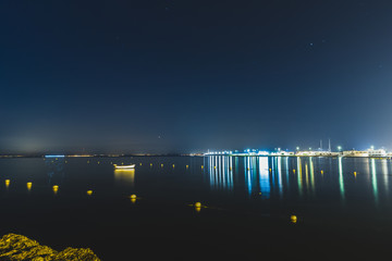 beautiful lights of the city at sunrise with a blue light on the water and the sky © Alberto