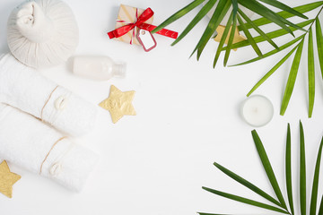 Christmas spa tropical mockup: white towels, Thai massage bags, golden stars and green fern leaves with gift boxes on background. New year gift concept. Text space © Evlira