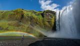 Frau steht in Regenbogen vor gewaltigem Wasserfall auf Island
