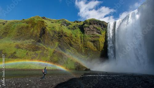 Frau steht in Regenbogen vor gewaltigem Wasserfall auf Island - 218066137