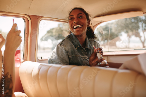 Fridge magnet Cheerful woman traveling by car with friends