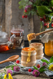 honey drips from a spoon into a wooden bowl - 218098595