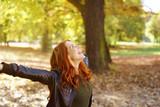 lachende junge frau mit roten haaren breitet ihre arme aus  während eines spaziergangs im wald © contrastwerkstatt