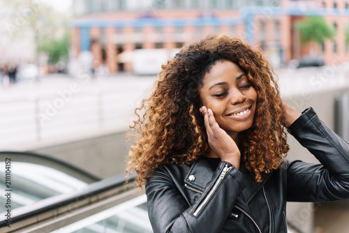 Wall mural Smiling black woman listening music on earphones