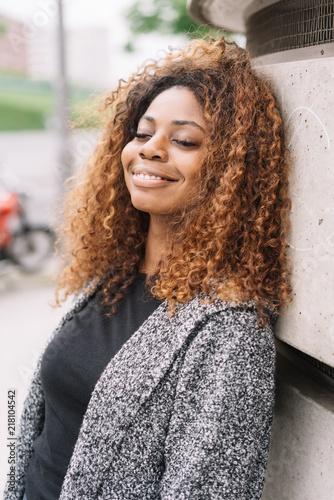Foto Murales lächelnde frau lehnt lächelnd und mit geschlossenen augen an einer wand