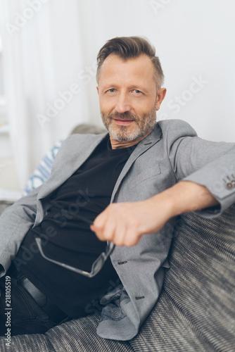 Foto Murales älterer mann mit jacket sitzt auf dem sofa