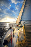 Sailing at sunset. A view from the yacht's deck to the bow and sails. Colorful evening sky over the Baltic sea - 218123129