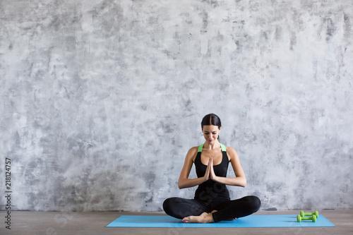 Wall mural Beautiful young woman in black meditating