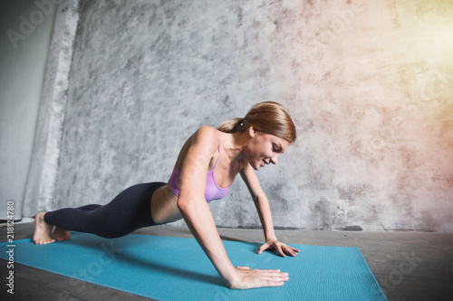 Plexiglas Fitness Young woman in a pink top working out sunlight effect