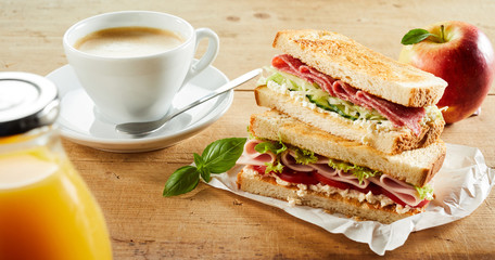 Cup of coffee and sandwich with ham on table