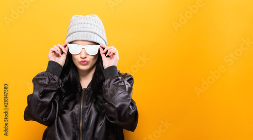 Leinwanddruck Bild Fashionable woman with attitude in bomber jacket and sunglasses on a yellow background
