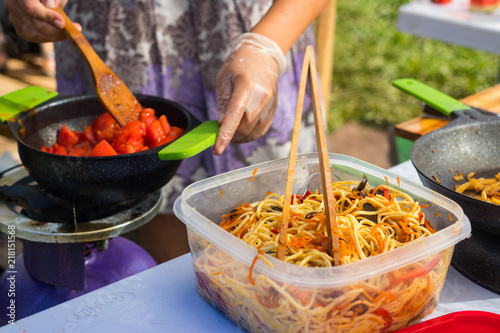 Cooking And Preparing Spicy Asian Noodle In Take Out Paper Bowl Box