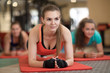 Leinwanddruck Bild - Attractive young girls leaning on their arms doing exercise for buttocks muscles at gym