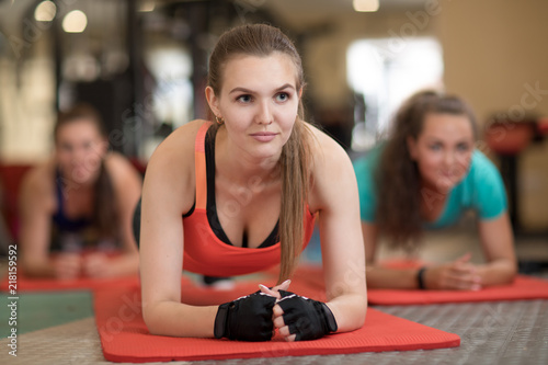 Leinwanddruck Bild Attractive young girls leaning on their arms doing exercise for buttocks muscles at gym