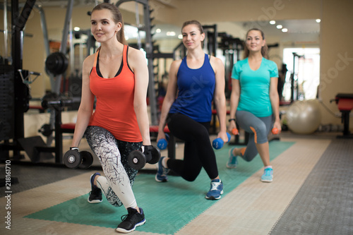 Leinwanddruck Bild Group of happy women with dumbbells flexing muscles in gym. Concept of sport, training, fitness, health and lifestyle.