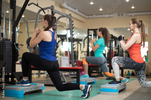 Leinwanddruck Bild Group of young girls flexing muscles in gym. Concept of sport, fitness, health and lifestyle.