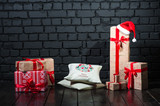 The concept of New Year's magic. Many boxes of Christmas gifts on the background of a black dark brick wall. Big gifts, a Santa Claus hat, a pillow with the inscription Happy Christmas