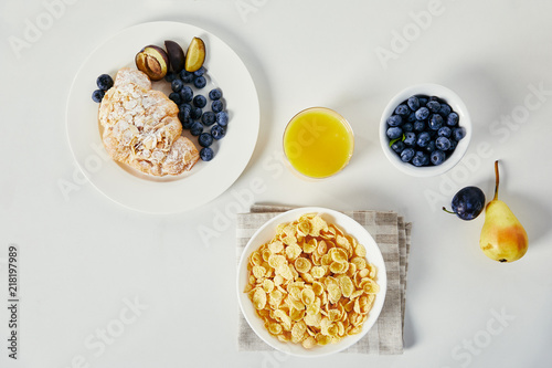 Leinwanddruck Bild flat lay with corn flakes in bowl, glass of juice and croissant with blueberries and plum pieces for breakfast on white tabletop